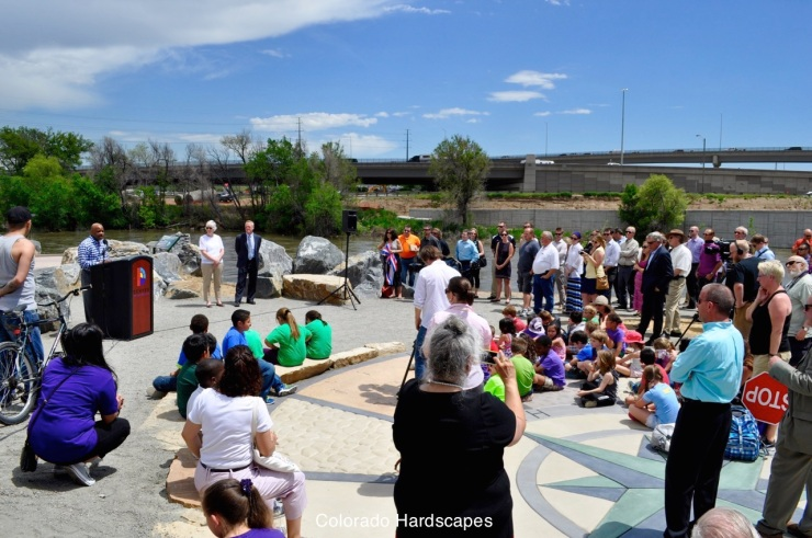 At the ribbon cutting ceremony, the mayor spoke while the community sat and stood near the custom concrete compass rose plaza